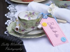 Handmade bride-to-be name tag with ribbon and button for vintage tea party hen do with teacup, saucer and side plater