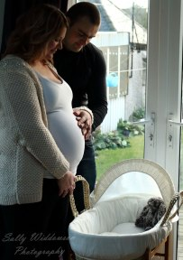 Pregnant couple and Moses basket bassinet waiting for baby for indoor maternity photography session