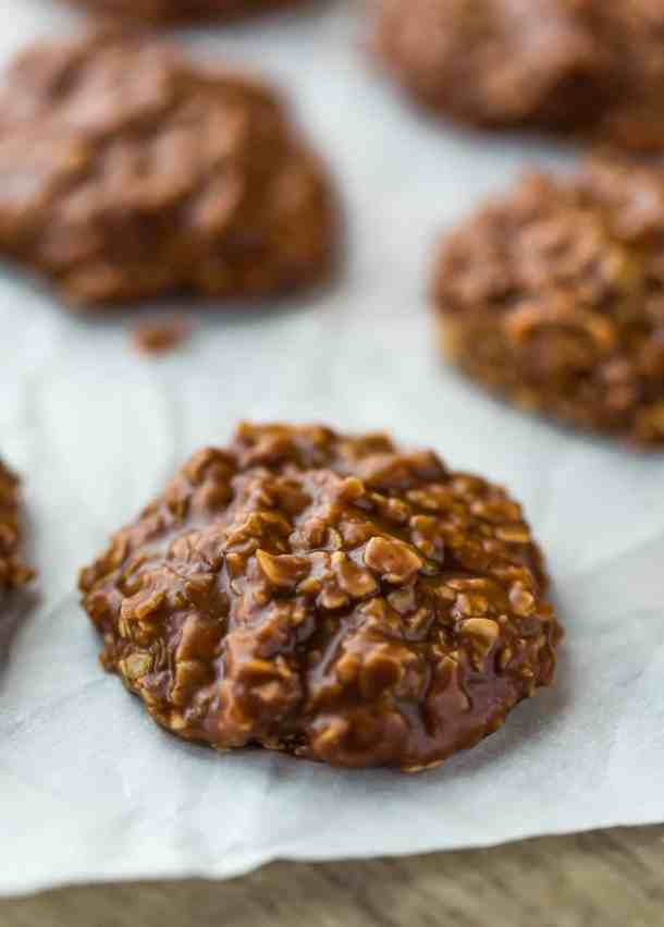 Close up of the most delicious chocolate peanut butter oatmeal no-bake cookie, sitting on white parchment paper.