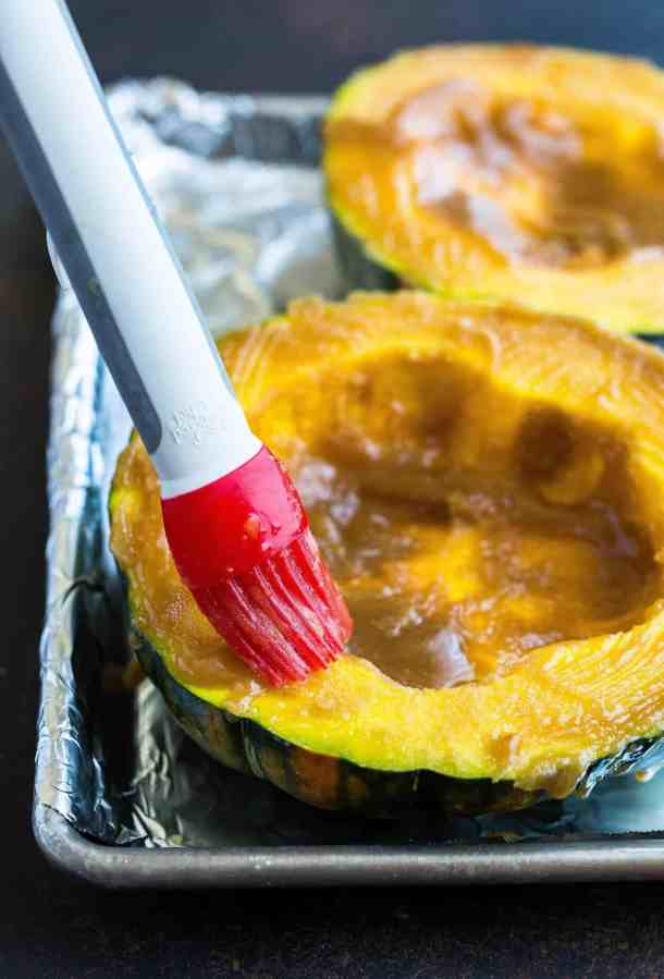 A red colored pastry brush is used to apply the buttery brown sugar mixture to the surface area of the winter squash.
