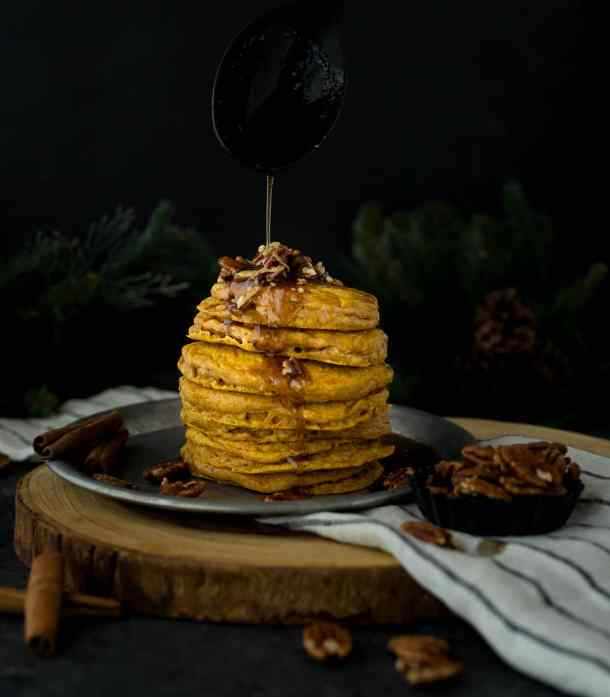 Cinnamon Brown Butter Syrup drizzled over a stack of pumpkin pancakes.