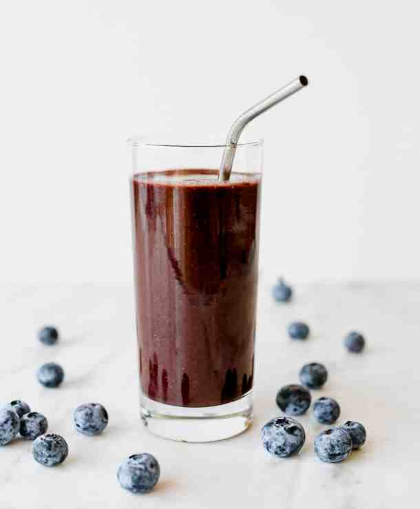 Healthy Acai Smoothie in a tall glass with blueberries around the base of the drink.