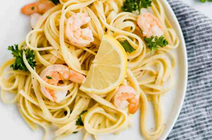 Shrimp Scampi with Linguini and a lemon wedge.
