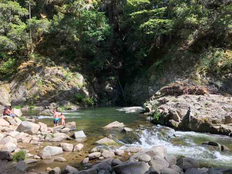 swimming hole in a river surrounded by cliffs and foliage