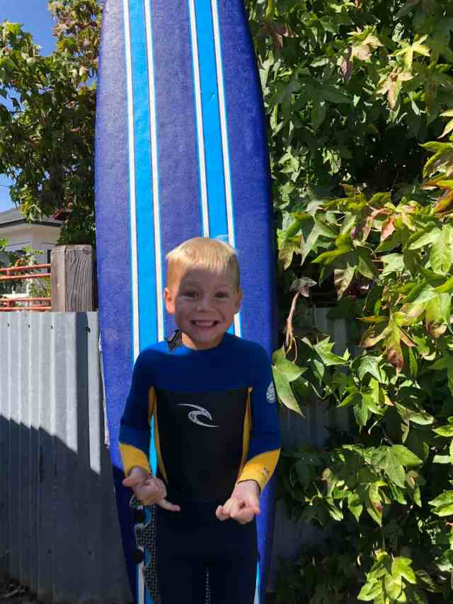 young blond boy in a wetsuit smiling and standing in front of a blue wetsuit