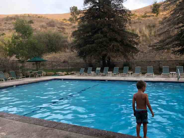 the pool at el capitan canyon is nestled against the grassy hills and has plenty of lounge chairs for relaxing in the afternoon