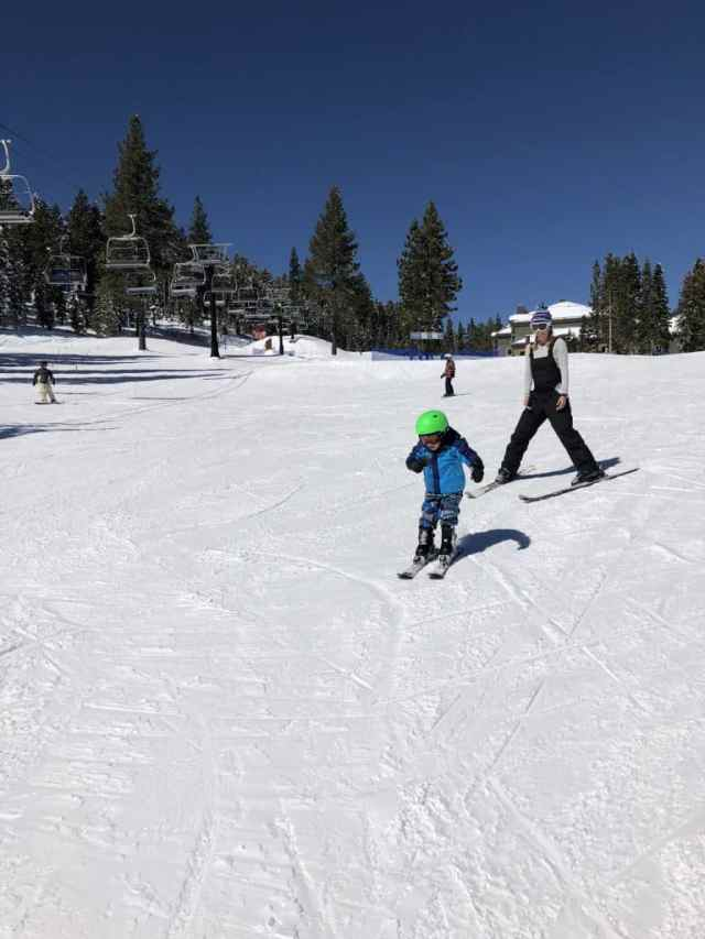 mother skiing behind a young boy on skis with a green helmet