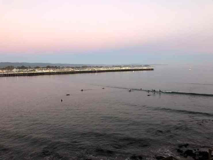 sunset with the santa cruz wharf in the background. people surfing a little wave