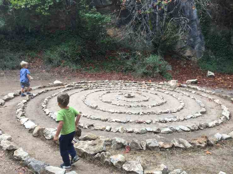two little boys walking in a spiral maze made of rocks. Pogonip County Park in Santa Cruz. A dog friendly hike in Santa Cruz that's great for kids too
