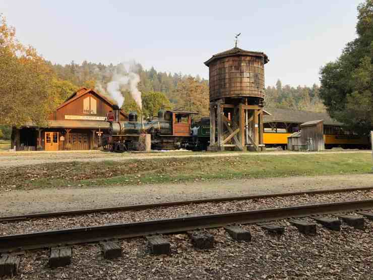 steam train parked in front of a water tower
