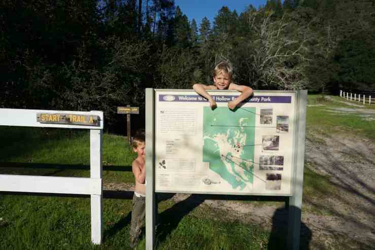 Two shirtless young boys standing next to a trail map at Quail Hollow Ranch in Felton. CA