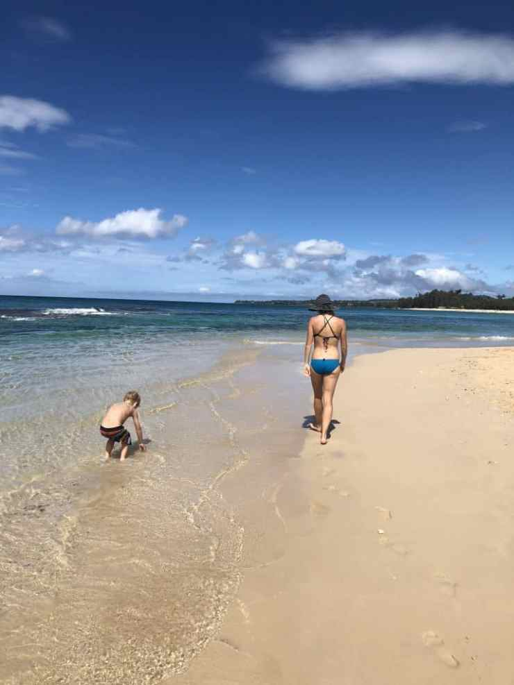 mom and son walking on a sandy stretch of beach in maui
