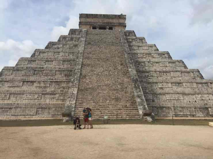 A mother, father holding a small child and a little boy in a stroller in front of Mayan ruins.