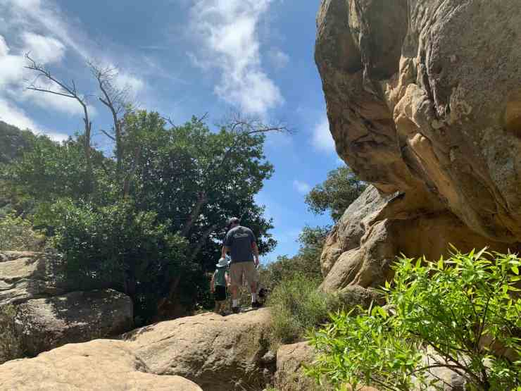 dad and small son walking past big boulders on the Seven Falls trail in Santa Barbara