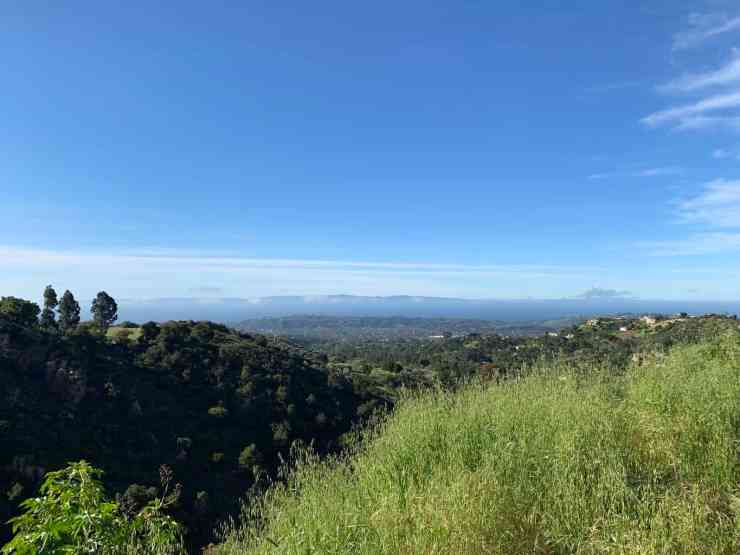Grassy hills with a view of the Channel Islands in the distance. Hiking is one the best things to do in Santa Barbara with a dog