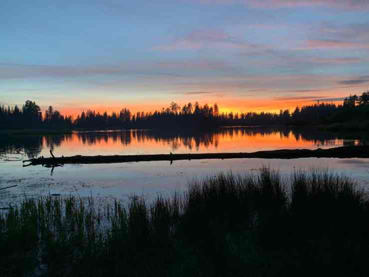 A spectacular sunset over Manzanita Lake in Lassen National Park. Orange sky with wispy clouds.