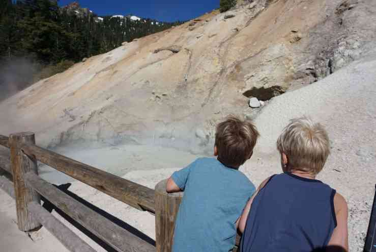 Two boys leaning on a fence looking at a steaming mud pot in Lassen National Park
