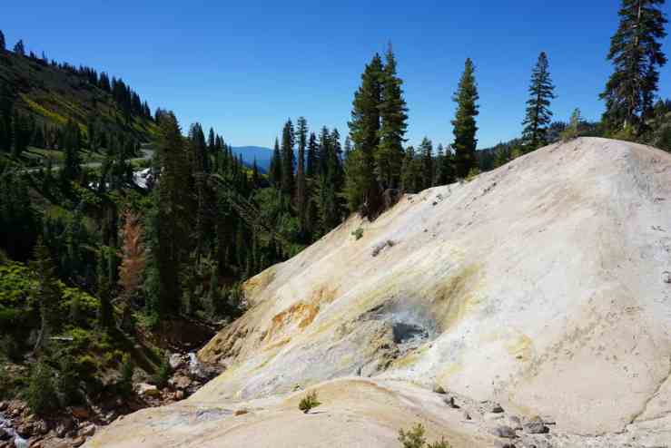 A barren hillside with a boiling mud pot in Lassen National Park