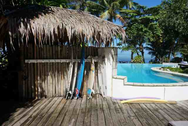 surf boards lined up against a wall next to a pool with the ocean in the background.  the perfect place to realize on your fiji surf trip