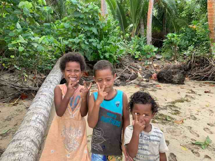 Three Fijian kids smiling on the beach. A highlight of a Fiji surf trip is the friendly locals