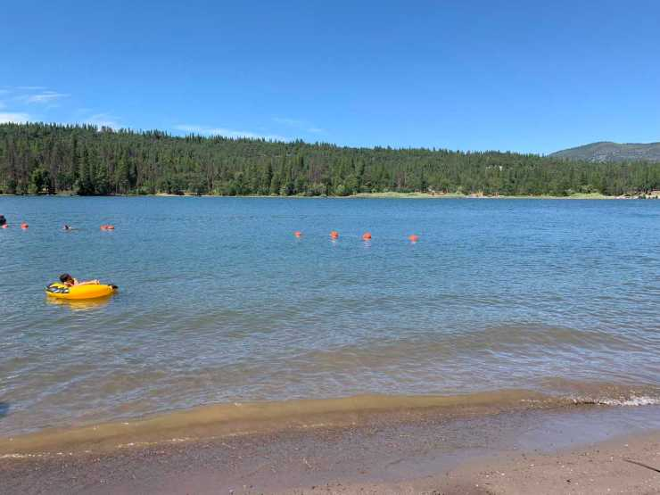 Lake Briton in McArthur Burney Falls is a warm lake for boating and swimming near Lassen National Park. Person in yellow inner tube floating inside a swimming area in an alpine lake