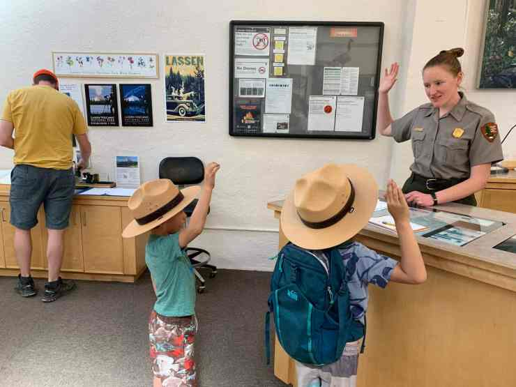 Two boys with their right hands raised getting sworn in by a national park ranger to be junior rangers in Lassen National Park