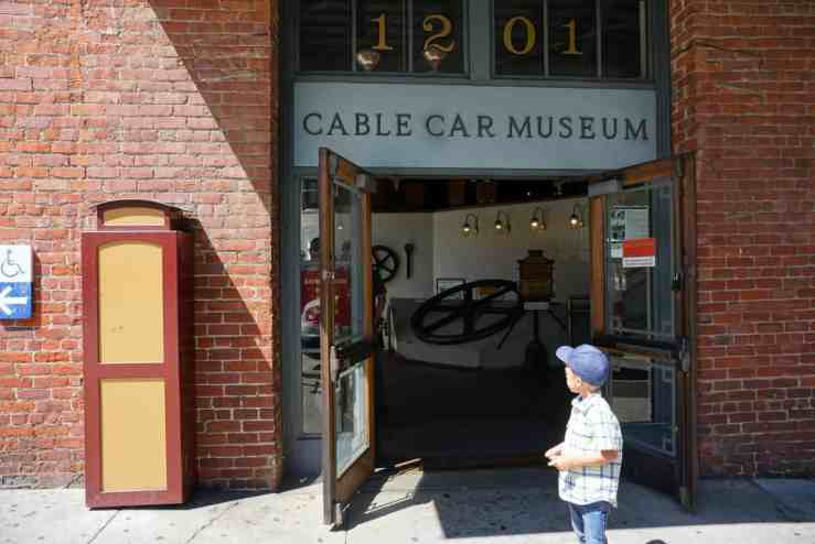 A boys standing outside the cable car museum in San Francisco CA