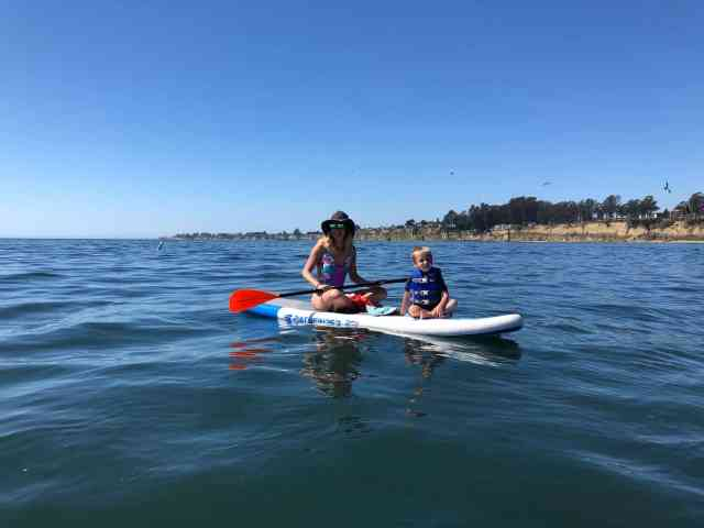 Mother and boy sitting on an inflatable SUP on the calm ocean