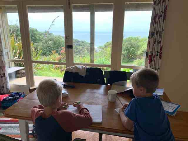 kids doing homework in a rustic airbnb dining room overlooking the surf break in raglan