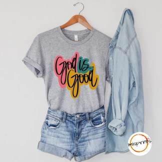 "Mock-up of a gray tee featuring ""God is Good' in a black script with bright pink, teal, and yellow surrounding the letters."