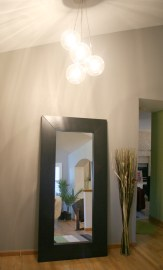Foyer - Next to the sun room, we repainted to a light modern grey, and added a modern chandelier and large floor mirror
