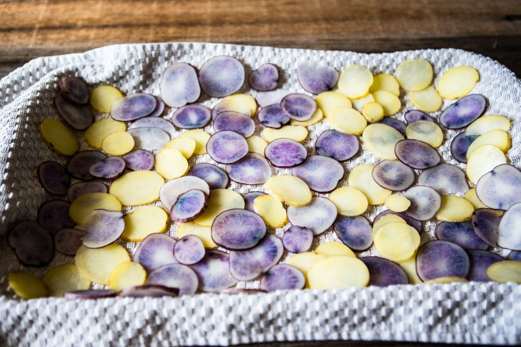 Place sliced potatoes on a sheet pan covered with a kitchen towel to dry.