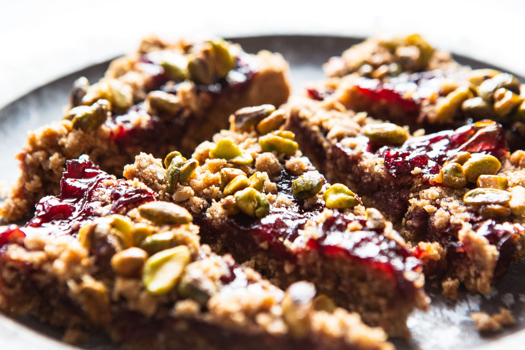 Serve your guests little tart triangles of cherry jam, pistachios and delightful vegan crumble.