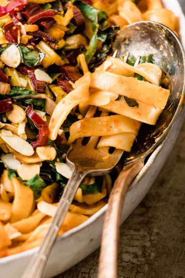 This tuscan pasta feast is a quick way to get extra veggies. Rich roasted red pepper pasta with bitter wilted Italian green and toasted almonds.