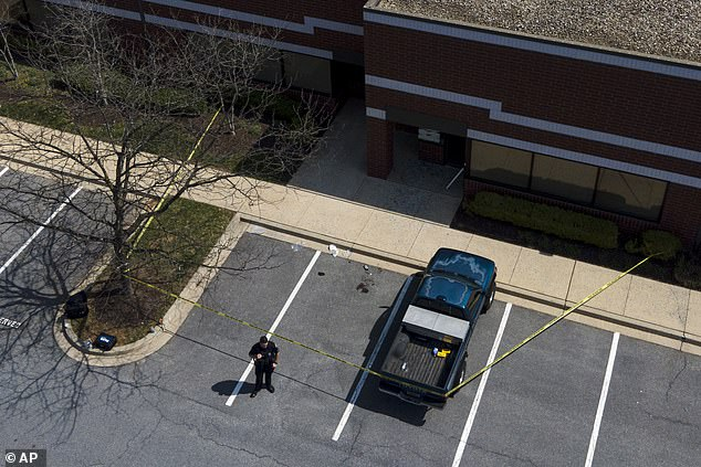 Fantahun Girma Woldesenbet, 38, who had a rank of E-4, or petty officer third class, entered a business at the Riverside Tech Park, which is connected to the Fort Detrick base, causing people inside to flee, police said. An officer stands near a pool of blood from the scene