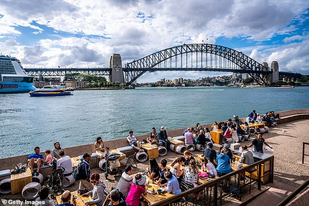 The Brewers Association is calling for Scott Morrison to slash the tax in half, a move that could save a small pub $465 each week. Pictured: Drinkers at the Sydney Opera House