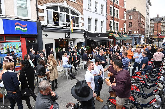 Revellers are pictured in Soho, central London in July last year as pubs, bars and restaurants reopened following the first lockdown