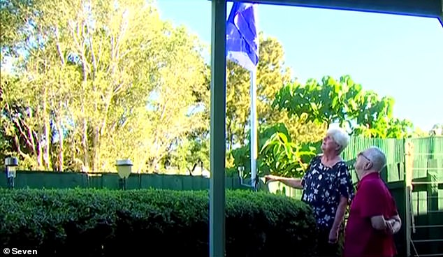 The couple say a neighbour has complained it is an 'eyesore' and that the body corporate has told them to lower it because raising the flag is in breach of building by-laws