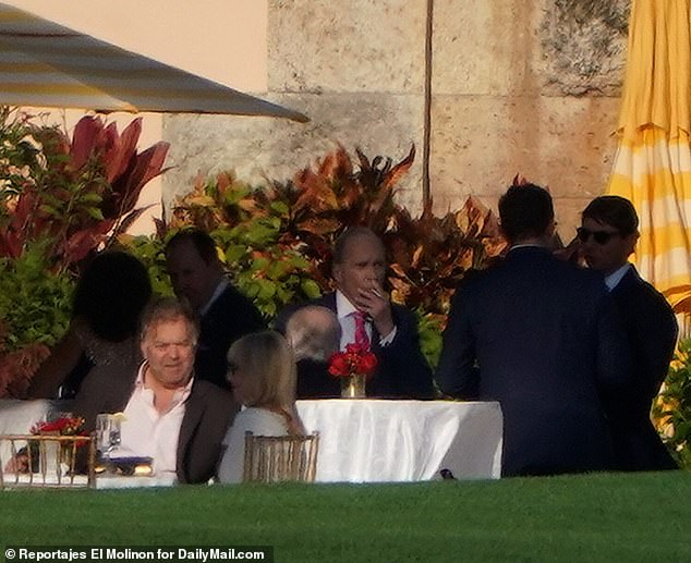 Larry Kudlow, center, is seen smoking a cigaretteat Mar-a-Lago during a party for the Conservative Partner Institute on Thursday