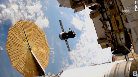 The Soyuz spacecraft can be seen during flight in the middle of this image.