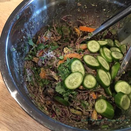 Rainbow Crunch Salad tossed with raw veggies, kelp noodles, and jalapeño ginger peanut sauce