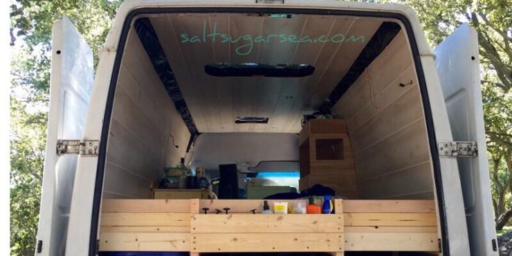 Van conversion bed frame headboard with custom built wood shelf for storage