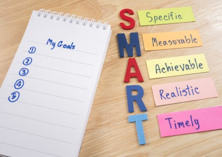 SMART Goals and My Goals in notebook on wood background (Business Concept)