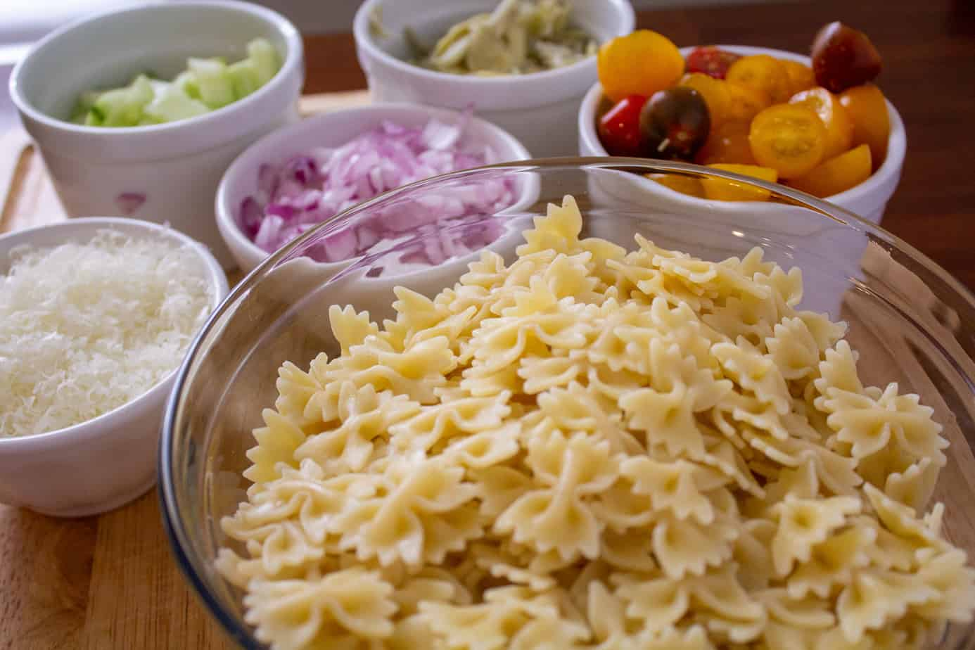 pasta, red onions, cherry tomatoes in bowls on a cutting board