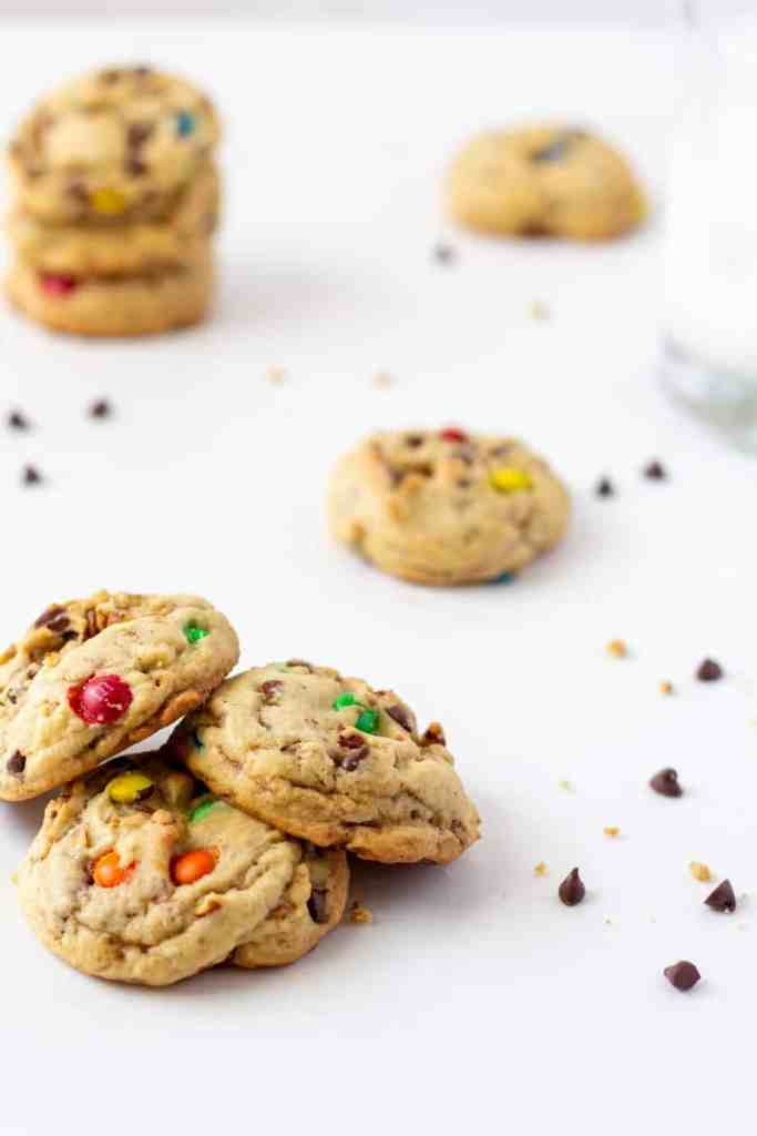 chocolate chip cookies on a white background with chips and cookies behind