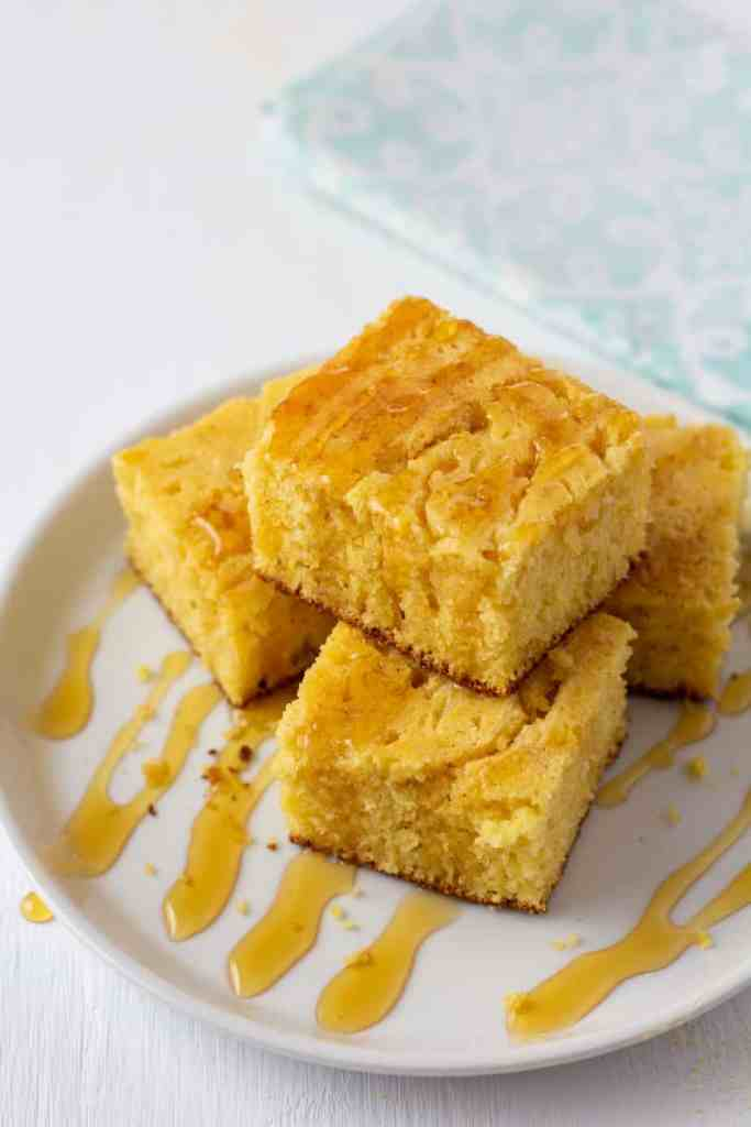 cornbread drizzled in honey on a white plate
