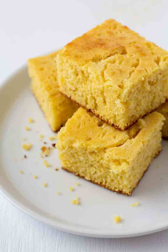 stacked cornbread pieces on a white plate
