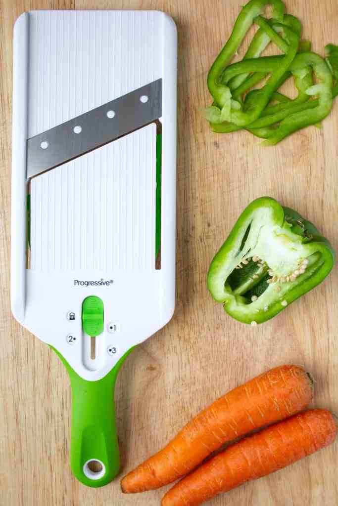 mandoline, green peppers, and carrots on a cutting board