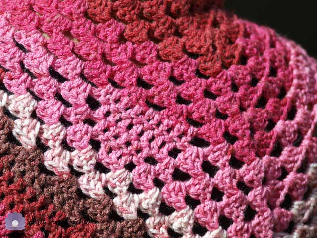 Close up view of the heart pattern in this granny triangle shawl.