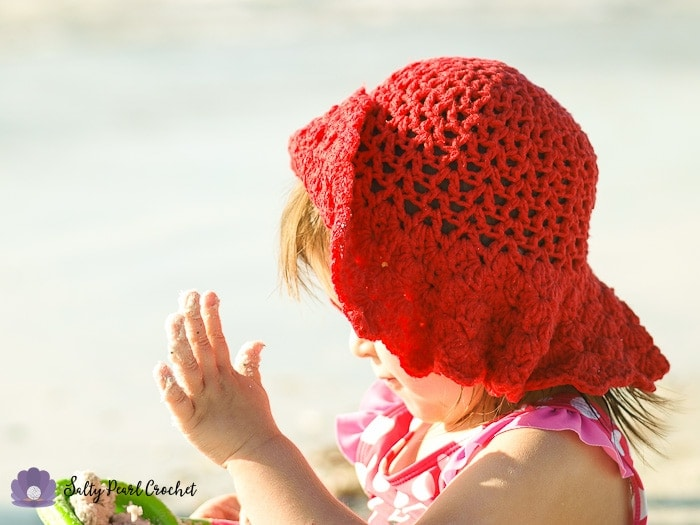 My daughter plays in the sand while wearing her Scalloped Toddler Beach Hat